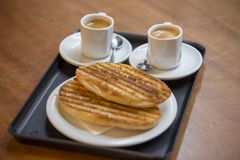 Cup of espresso with slices of bread. Cup of espresso coffee with fat slices of bread and butter Stock Photos