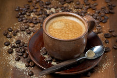 Cup of espresso, sugar and coffee beans on wooden table Stock Photography