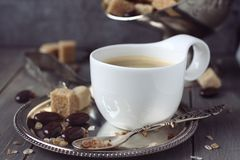 Cup of espresso, sugar cubes and chocolate candy on rustic wooden background Stock Images