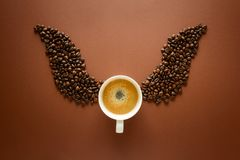 Cup of espresso with wings from coffee beans on brown background. Good morning concept. Top view. Flat lay. Caffeine gives you wings royalty free stock photos