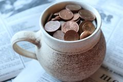 Cup of euro cents. Ceramic mug of euro cents on old newspaper royalty free stock image