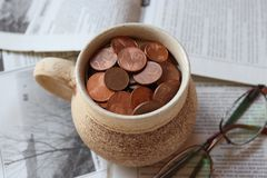 Cup of euro cents with glasses. Cup of euro cents and glasses on old newspaper royalty free stock photos