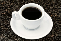 Black Coffee and Beans. A cup filled with black coffee with matching plate on background of coffee beans. Shot from high angle Royalty Free Stock Photo