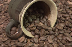 Cup filled with coffee beans. Brown cup filled with coffee beans against wooden background royalty free stock images
