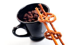 Cup filled with coffee beans amd pretzels Stock Image