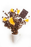 Cup filled coffee beans with chocolate and orange. On white background Royalty Free Stock Photography