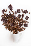 Cup filled coffee beans with chocolate on white. Coffee cup filled with coffee and beans with jute on white background Stock Images