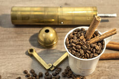 Cup filled with coffee beans, cinnamon and grinder on wooden table Stock Image