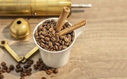 Cup filled with coffee beans, grinder and cinnamon on wooden table Stock Image