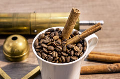 Cup filled with coffee beans, grinder, turk and cinnamon on wooden table Royalty Free Stock Photo