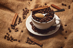 Cup filled with coffee beans and spoon with brown sugar Royalty Free Stock Photography
