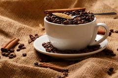 Cup filled with coffee beans and spoon with brown sugar Royalty Free Stock Images