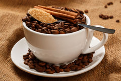 Cup filled with coffee beans and spoon with brown sugar Stock Photo