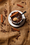 Cup filled with coffee beans and spoon with brown sugar Stock Image
