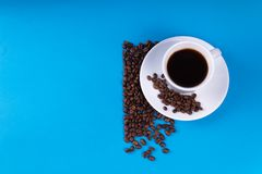 A cup filled with coffee next to it is filled with coffee beans, half of the background is left blank.  stock images