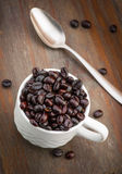 Cup filled with roasted coffee beans Stock Images