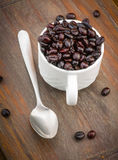 Cup filled with roasted coffee beans Royalty Free Stock Image