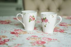 Cup on a floral tablecloth kitchen setting Stock Image