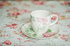 Cup on a floral tablecloth kitchen setting Royalty Free Stock Photography
