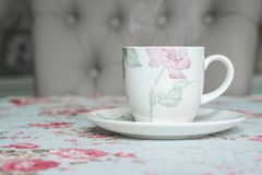Cup on a floral tablecloth kitchen setting Stock Photos