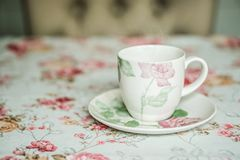 Cup on a floral tablecloth kitchen setting Royalty Free Stock Image