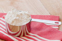 Cup of flour. A measuring cup of flour sits on a red striped towel Royalty Free Stock Photo