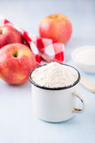Cup of flour, butter, red apples and sugar Stock Photography