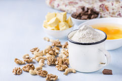 Cup of flour, eggs, butter, nuts and chocolate chunks Stock Photos