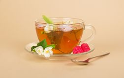 Cup of flower tea spoon and raspberry on beige Royalty Free Stock Photo