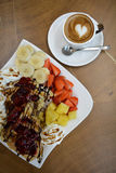 Cup of foamy cappuccino and waffles with fruit and cream Royalty Free Stock Photos