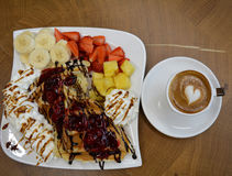 Cup of foamy cappuccino and waffles with fruit and cream Royalty Free Stock Image