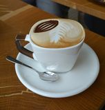 Cup of foamy cappuccino on a wooden table Royalty Free Stock Images