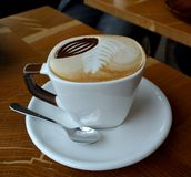 Cup of foamy cappuccino on a wooden table Royalty Free Stock Photo