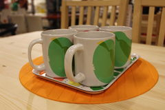 The cup. The four appliance with the cup of coloured drawing or pattern on the desk Royalty Free Stock Image