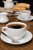 Cup of fragrant black coffee on the table with milk and a bun Royalty Free Stock Image