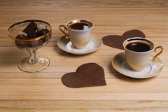 A cup of coffee and chocolate candy on a wooden surface Royalty Free Stock Images
