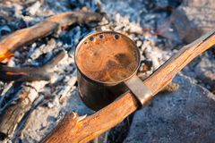 Cup of fragrant coffee with foam on a campfire, tourist morning Royalty Free Stock Photos