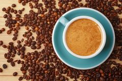 A cup of fragrant coffee in foam on a wooden table. Coffee beans stock photos