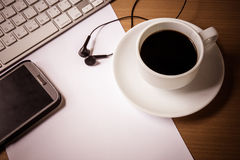 Cup of fragrant coffee on a morning paper and keyboard. On table Royalty Free Stock Photography