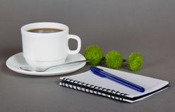 Cup of fragrant coffee and note. Cup of fragrant coffee, green chrysanthemums, a sketchpad and a ballpoint on a gray background Royalty Free Stock Photo