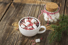 Cup of fragrant homemade cocoa with marshmallows and crushed red white candy topping. On the simple wooden textural Royalty Free Stock Photo