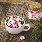 Cup of fragrant homemade cocoa with marshmallows and crushed red white candy topping. On the simple wooden textural Royalty Free Stock Photos