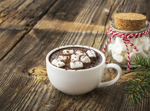 Cup of fragrant homemade cocoa with marshmallows and crushed red white candy topping. On the simple wooden textural Stock Photo