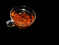 A cup of fragrant hot tea on a black background Royalty Free Stock Photos