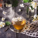 Cup of fragrant hot tea with Jasmine and fresh flowers, on wooden surface stock photo