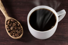 Cup French coffee on wooden table and a spoon full of beans. Hot Cup of French coffee on a wooden table and a spoon full of beans Royalty Free Stock Photography