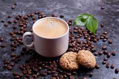 Cup of fresh americano and cookies on coffee beans background Royalty Free Stock Photo