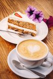 Cup of fresh cappuccino coffee with delicious piece of carrot cake on the wooden table royalty free stock images