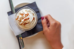Cup of a fresh caramel latte with whipped cream on table in coffee shop. Close Royalty Free Stock Photos