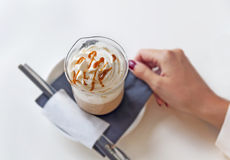 Cup of a fresh caramel latte with whipped cream on table in coffee shop. Close Stock Photo